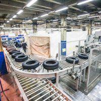 tyre production conveyor at bright new factory with workman